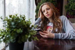 girl with phone looking sad